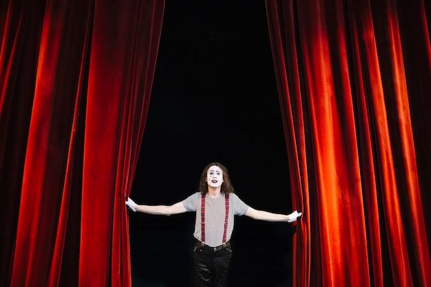 Artista masculino mímica no palco perto da cortina vermelha