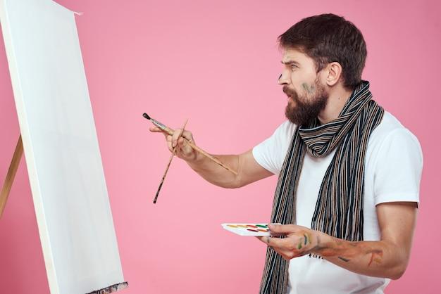 Artista masculino pinta uma imagem sobre tela com um cavalete