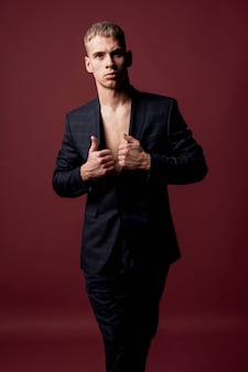 Artista masculino posando sedutoramente no terno