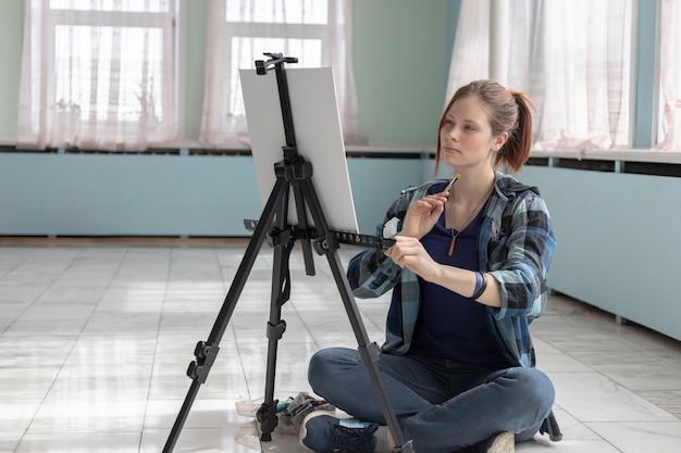 Artista menina pinta com tintas a óleo, sentado no chão de mármore. cavalete e lona branca ficam no chão de azulejos de mármore na sala com paredes verde-turquesa e verde claro.