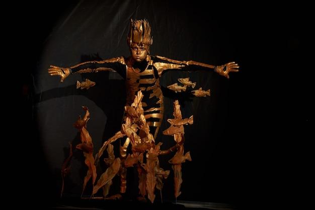 Artista mímico vestido com roupas pretas com elementos decorativos dourados em pé entre algas e peixes criados artificialmente que estão localizados ao seu redor. conceito de vida marinha e natureza