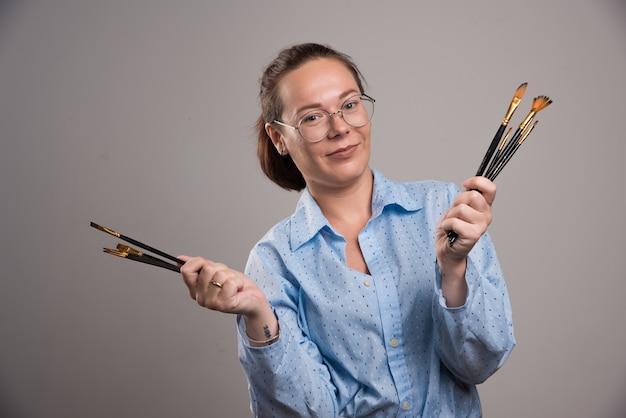 Artista mulher detém pincéis de pintura em fundo cinza. foto de alta qualidade