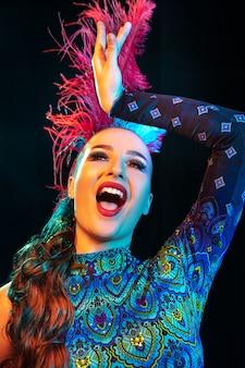 Artista. mulher jovem e bonita no carnaval, elegante traje de máscaras com penas em fundo preto em luz de néon. copyspace para anúncio. celebração de feriados, dança, moda. época festiva, festa.