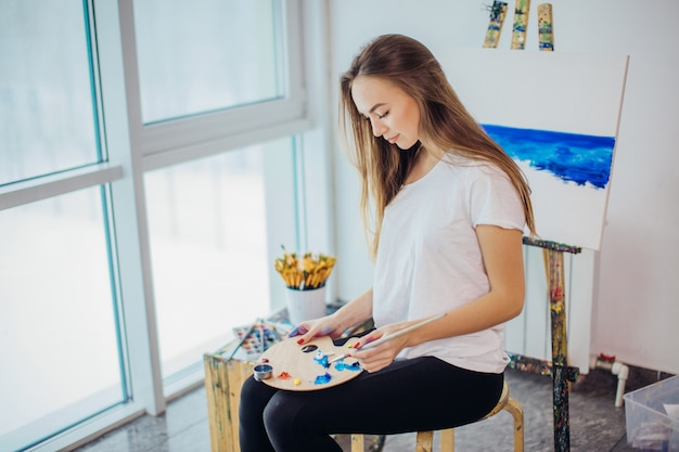 Artista mulher pintando uma imagem em um estúdio bem iluminado