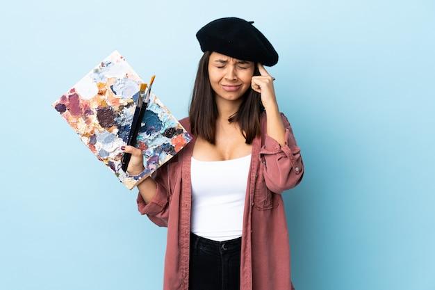 Artista mulher segurando uma paleta com dor de cabeça