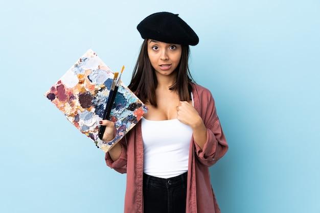 Artista mulher segurando uma paleta com expressão facial surpresa