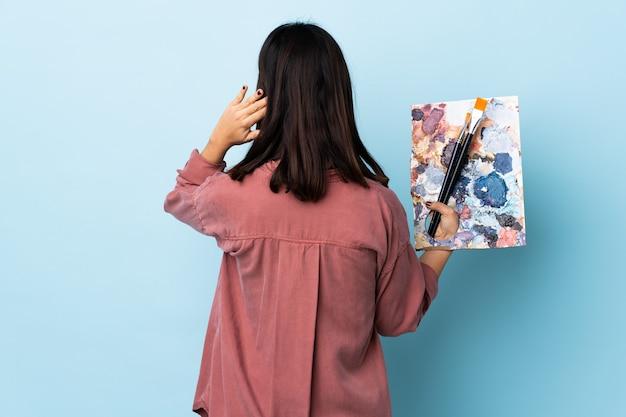 Artista mulher segurando uma paleta na posição traseira e pensando