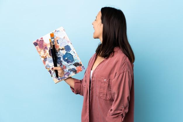 Artista mulher segurando uma paleta rindo em posição lateral