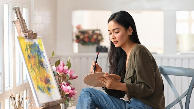 Artista mulher trabalha na pintura acrílica abstrata no estúdio de arte.
