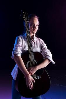 Artista no palco abraçando o violão