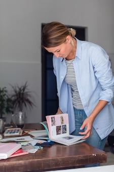 Artista olhando através do álbum na mesa