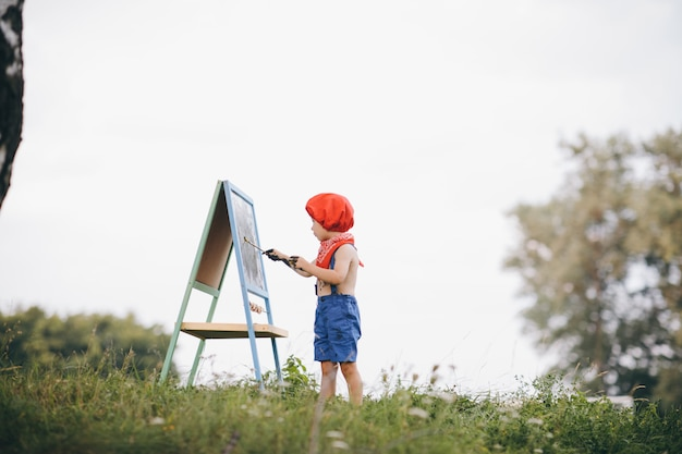 Artista pinta um pincel fino em uma tela. na foto, apenas a mão do artista, pincel e tela no cavalete