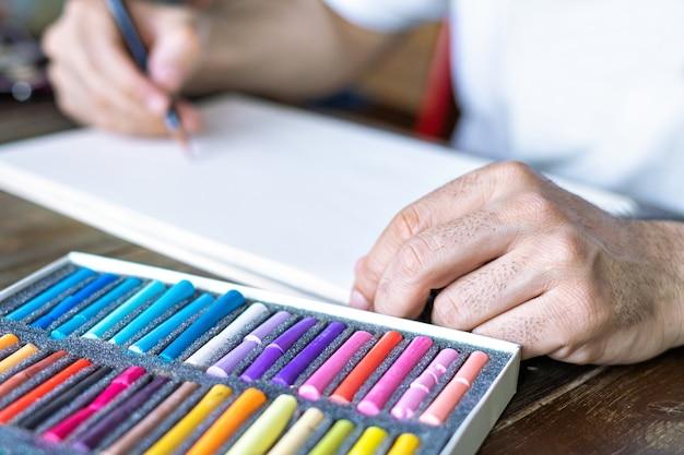 Artista pintando com um giz de cera pastel em uma folha de papel branca