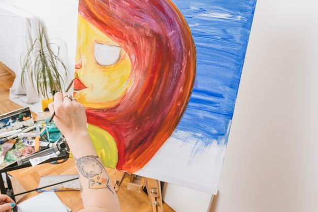 Artista pintando mulher em cavalete na oficina