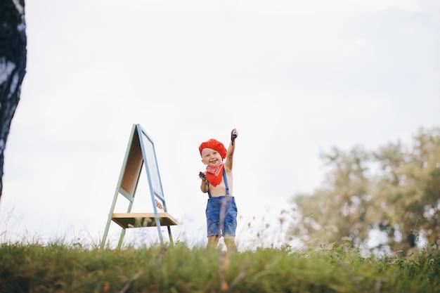 Artista pintando uma paisagem de verão. menino sobre a natureza do artista desenha