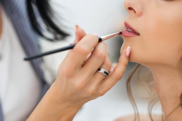 Artista profissional faz maquiagem pinta os lábios com um pincel com batom no rosto de uma jovem garota