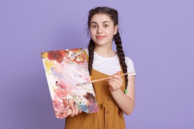 Artista profissional, sorrindo com paleta e pincel