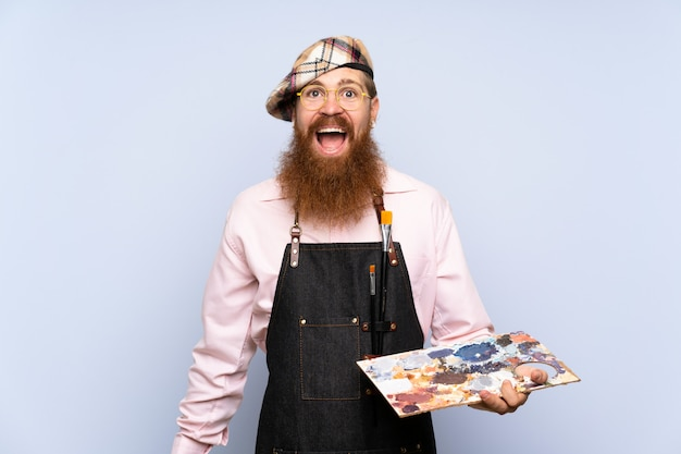 Artista ruiva homem com barba longa, segurando uma paleta sobre parede azul isolada com surpresa e expressão facial chocada