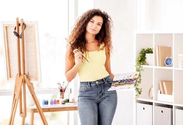 Artista segurando tintas e borla