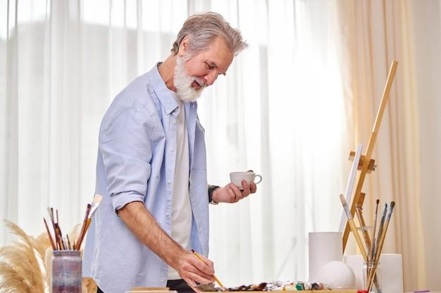 Artista sênior desenha um esboço no papel e bebe chá, aproveite o processo de trabalho no estúdio da sala de luz