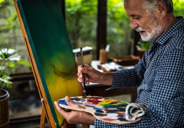 Artista sênior, pintura em um espaço de trabalho