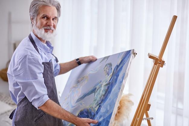 Artista sênior remove a tela do cavalete, pintura preparada nas mãos de um artista habilidoso. na sala iluminada