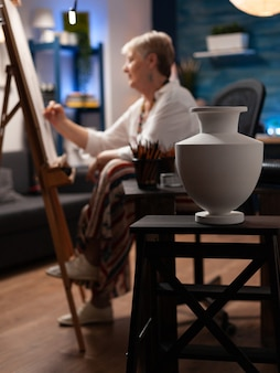 Artista sênior usando lápis e desenho de vaso na tela