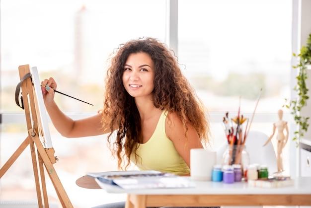 Artista sentado ao lado de cavalete