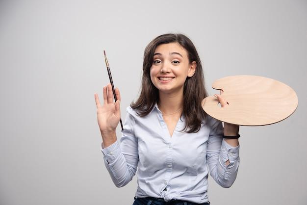 Artista sorridente segurando o pincel e a paleta sobre a parede cinza.