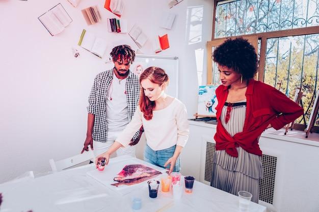 Artista talentoso. artista ruiva talentosa e criativa ensinando amigas a fazer pinturas em mármore