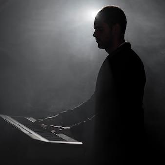 Artista tocando fumaça de piano e efeitos de sombras