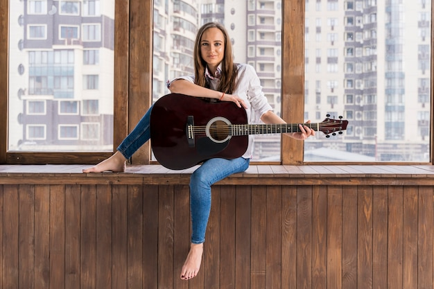 Artista tocando guitarra dentro de casa longa visão