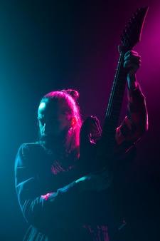 Artista tocando guitarra no palco, plano médio