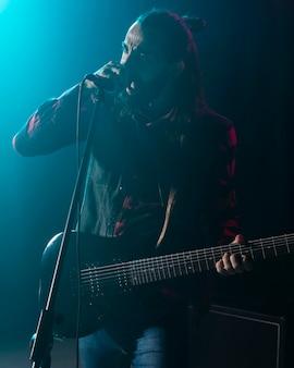 Artista tocando violão e cantando no microfone