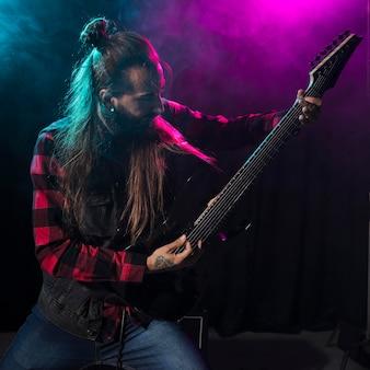 Artista tocando violão e olhando para o instrumento