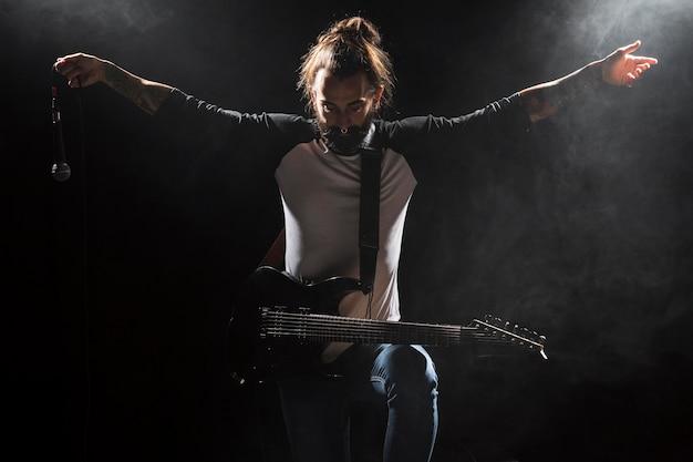 Artista tocando violão e segurando um microfone