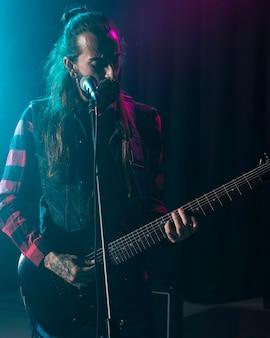 Artista tocando violão e tendo um microfone