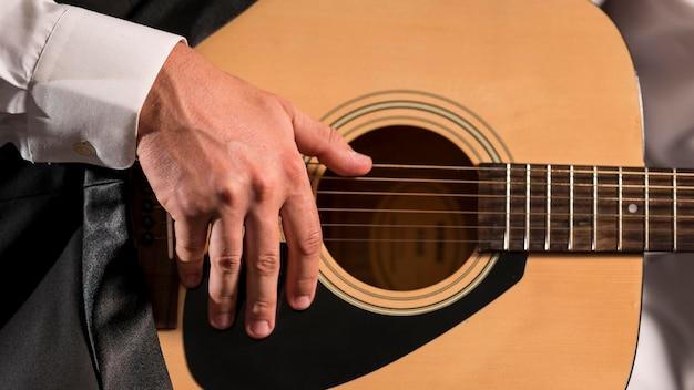 Artista tocando violão em close-up