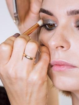 Artista trabalhando em maquiagem cliente