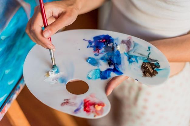 Artista usando tintas a óleo em palete com várias cores