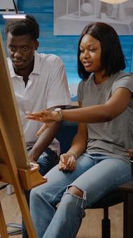 Artistas afro-americanos analisando desenho de vaso