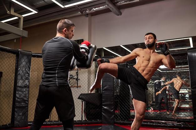Artistas de artes marciais mistas se socando, lutando sem regras na academia, treinando. boxeadores agressivos lutando, tendo músculos fortes e poderosos