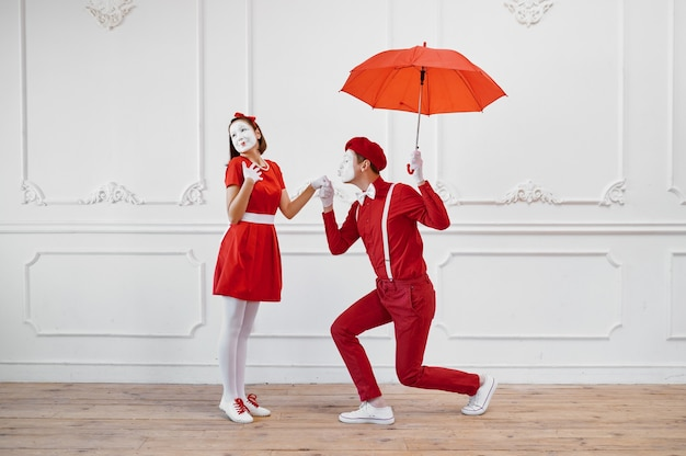 Artistas mímicos em trajes vermelhos, cena com guarda-chuva
