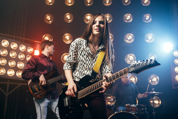 Artistas musicais no palco em boate, estilo vintage. guitarristas e baterista, show de banda de rock, show de música