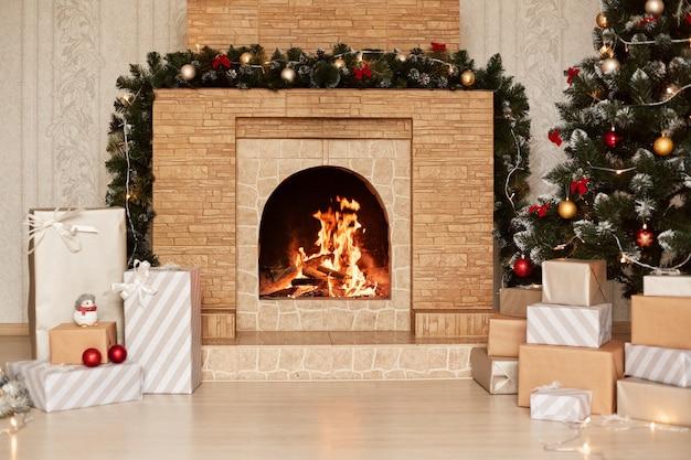 Árvore de ano novo e caixas de presente de natal no interior com lareira, sala de estar festiva, decoração de natal para celebração.