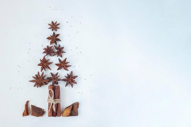 Árvore de ano novo feita de anis estrelado e paus de canela, fundo branco, vista de cima, espaço de cópia, ideia para um cartão de natal