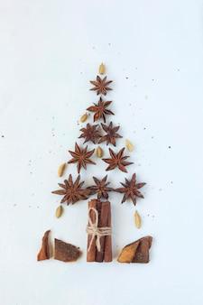 Árvore de ano novo feita de anis estrelado e paus de canela, fundo branco, vista de cima