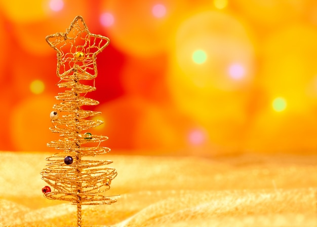 Árvore de arame dourado de natal em luzes desfocadas