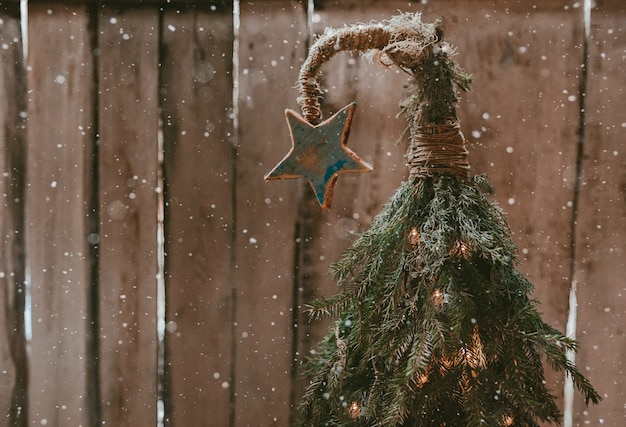 Árvore de natal artesanal com uma estrela em um topo curvo em uma parede de madeira. ano novo barato. estilo ecológico minimalista e moderno.