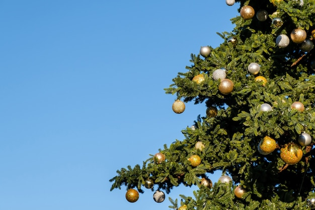 Árvore de natal artificial ao ar livre em um céu azul em um dia ensolarado de inverno.